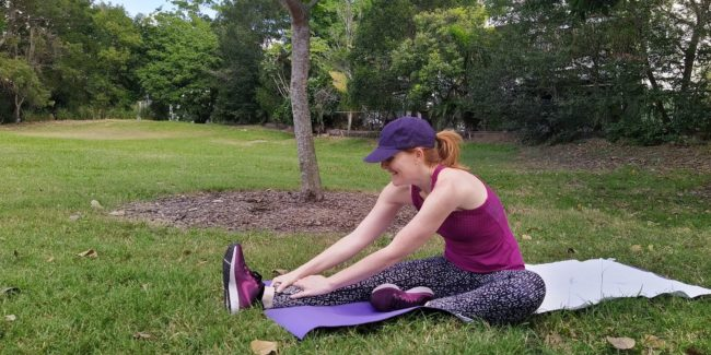 Woman doing leg stretches in a park
