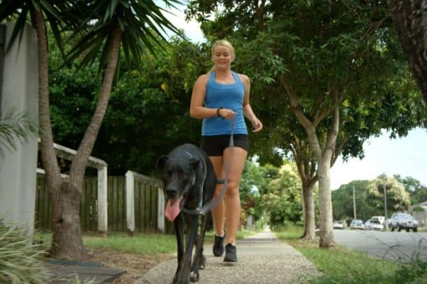 Young woman jogging with black dog