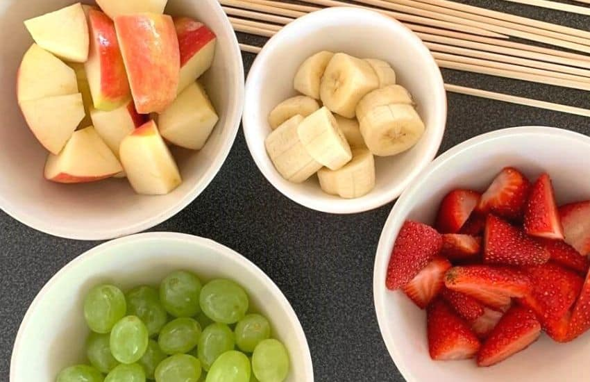Sliced apples, strawberries, bananas and grapes