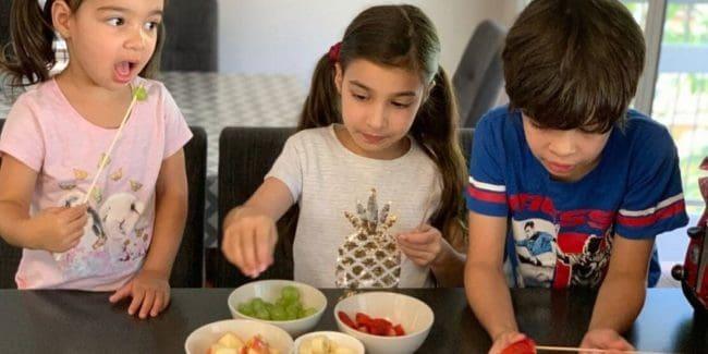 Three Queensland kids making and eating fruit kebabs