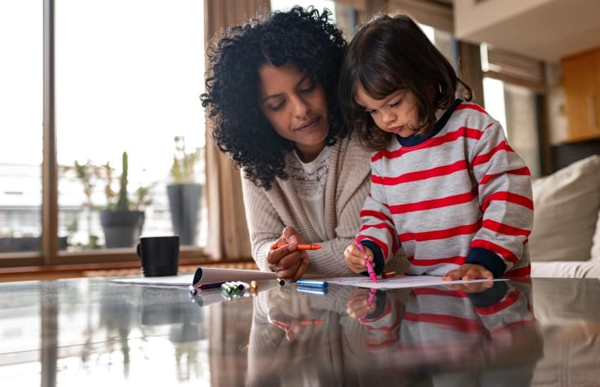 Mother and child colouring in at coffee table