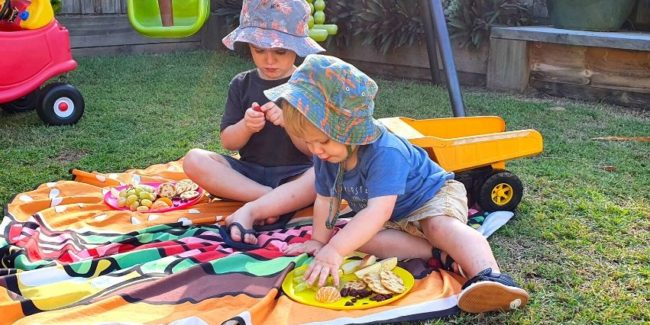 Two young brothers in Queensland eating healthy snacks in their backyard