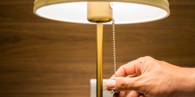 Close up of person's hand switching off a bedside lamp
