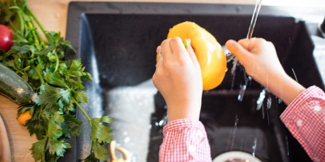 Child washing a yellow capsicum