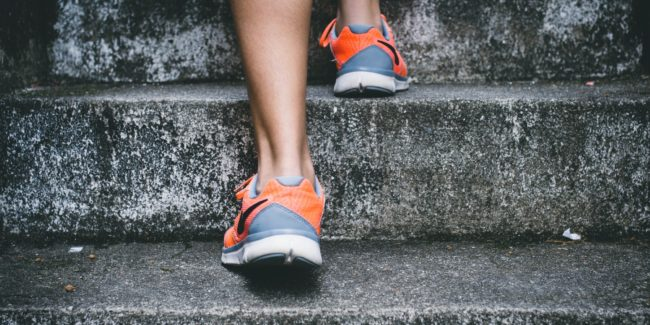 Close up of a person's feet as they jog up stairs