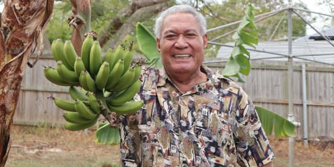Man smiling while holding a banana bunch in his backyard
