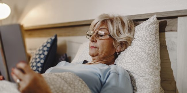 Mature women reading in bed