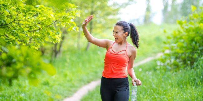Woman walking in nature and waving at someone