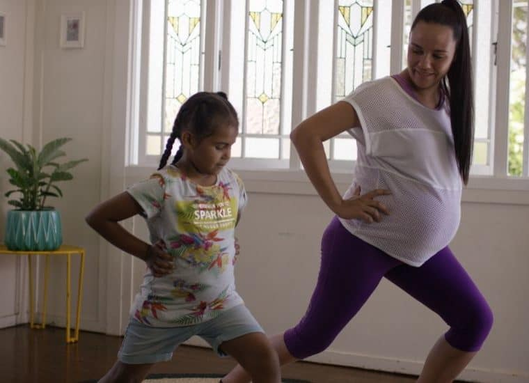 Pregnant woman and her daughter doing light exercise in their house
