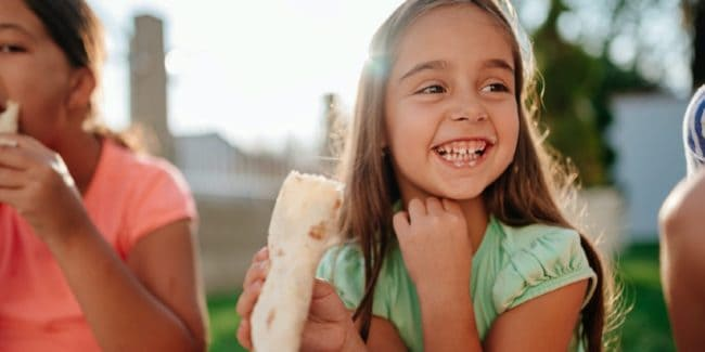 Young girl eating wrap and smiling