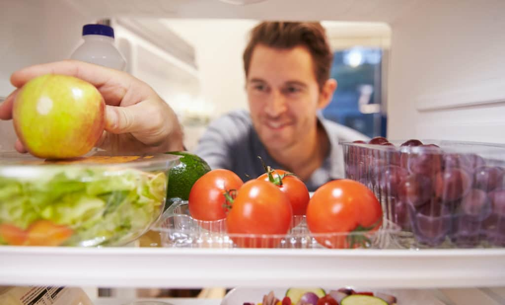 Man reaching inside fridge for a piece of fruit