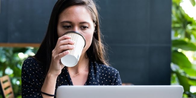 Woman drinking coffee while looking at computer