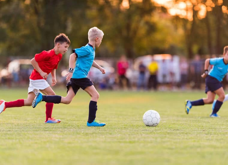 Boys playing soccer on a soccer field