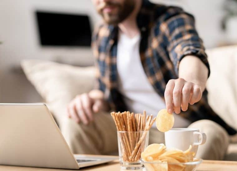Man snacking in front of laptop