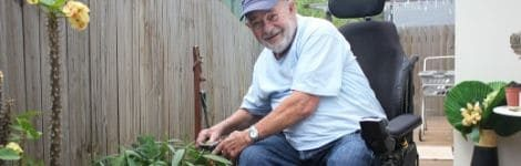 Smiling Queensland man in wheelchair, gardening in backyard